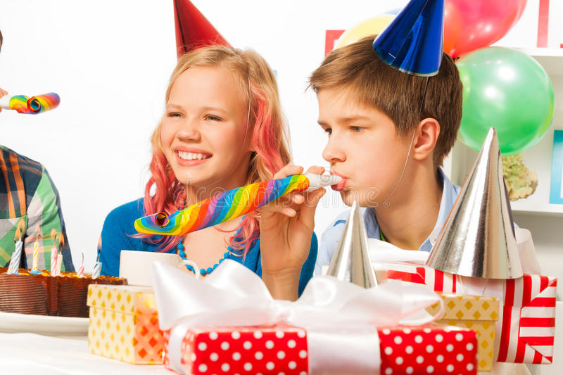 Funny and happy birthday party with teen friends. Happy birthday party with smiling teen girl and friends blow noisemaker blower horns royalty free stock images