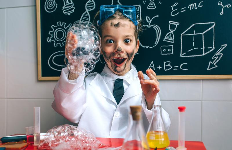 Funny boy chemist with dirty face. Funny happy boy dressed as chemist with dirty face after doing an experiment royalty free stock images