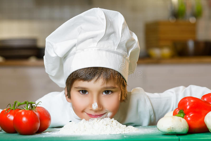 Funny happy chef boy cooking at restaurant kitchen. And bent over the flour stock photos