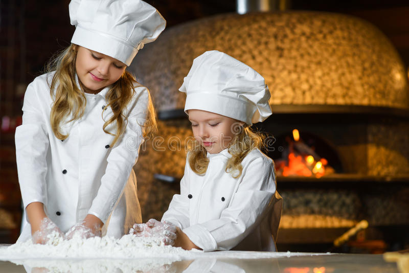 Funny happy chef boy width girl cooking at. Restaurant kitchen and knead the dough stock image