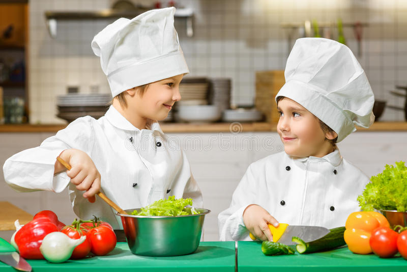Funny happy chef boys cooking at restaurant. Kitchen stock photography