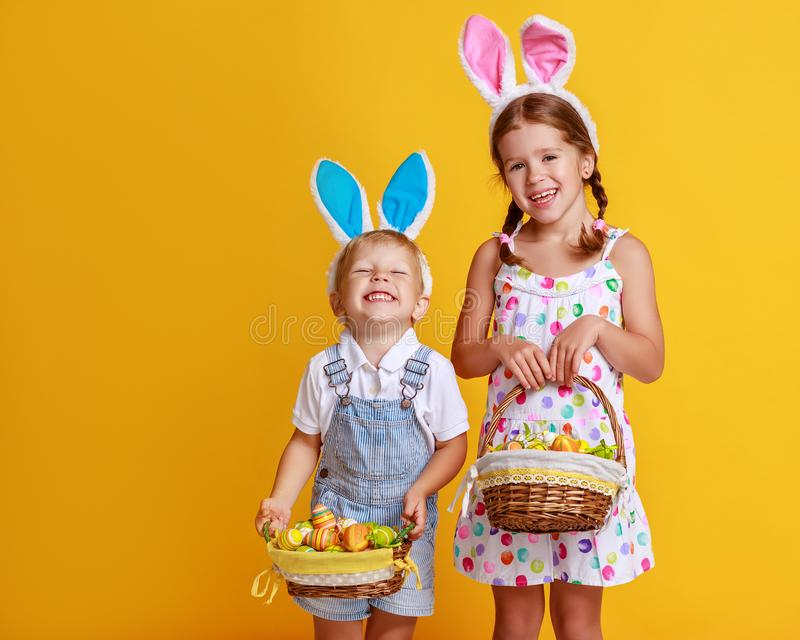 Funny happy children with easter eggs and bunny ears on yellow stock images