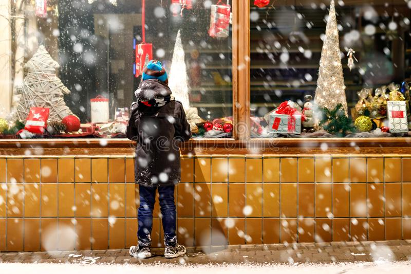 Funny happy child in fashion winter clothes making window shopping decorated with gifts, xmas tree. Cute little school kid boy on Christmas market. Funny happy royalty free stock photo