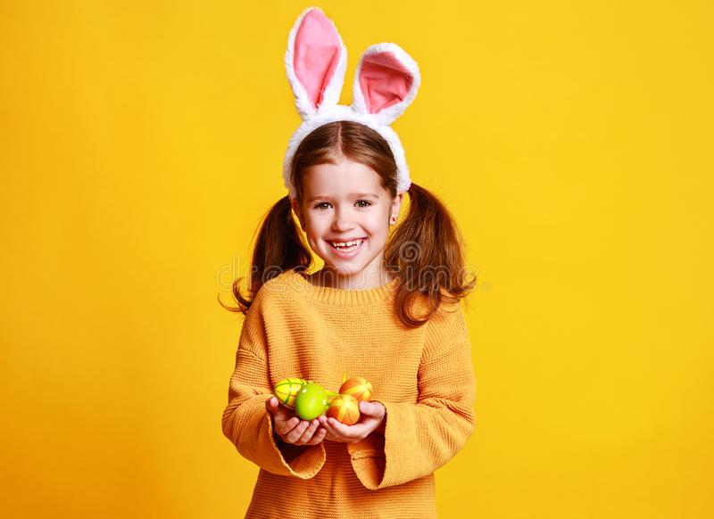 Funny happy child girl with easter eggs and bunny ears on yellow stock images