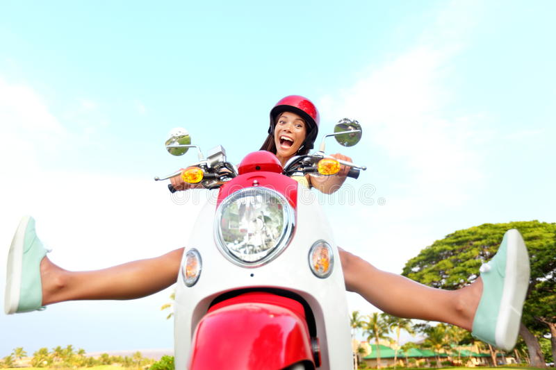 Funny happy free woman on scooter. Driving excited and cheerful. Mixed race Asian Chinese / Caucasian girl stock image