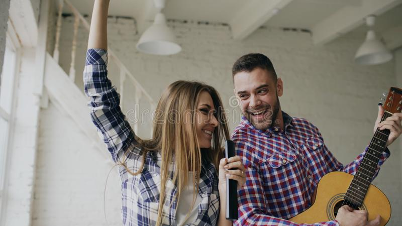 Funny happy and loving couple dance on bed singing with tv controller and playing guitar. Man and woman have fun during stock photo