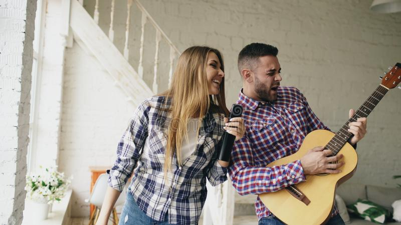 Funny happy and loving couple dancing and playing guitar. Man and woman have fun during their holiday at home stock image