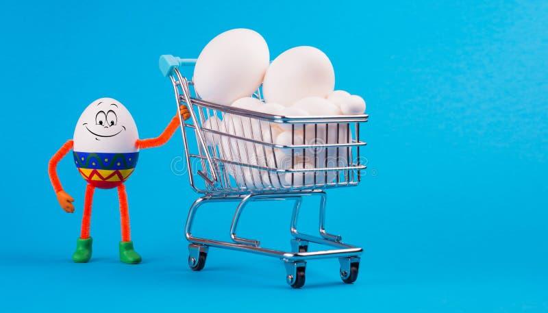 Easter egg near the cart full of chikken eggs. Funny happy smiling egg with Ester ornament standing near the cart from a supermarket full of chikken eggs stock images