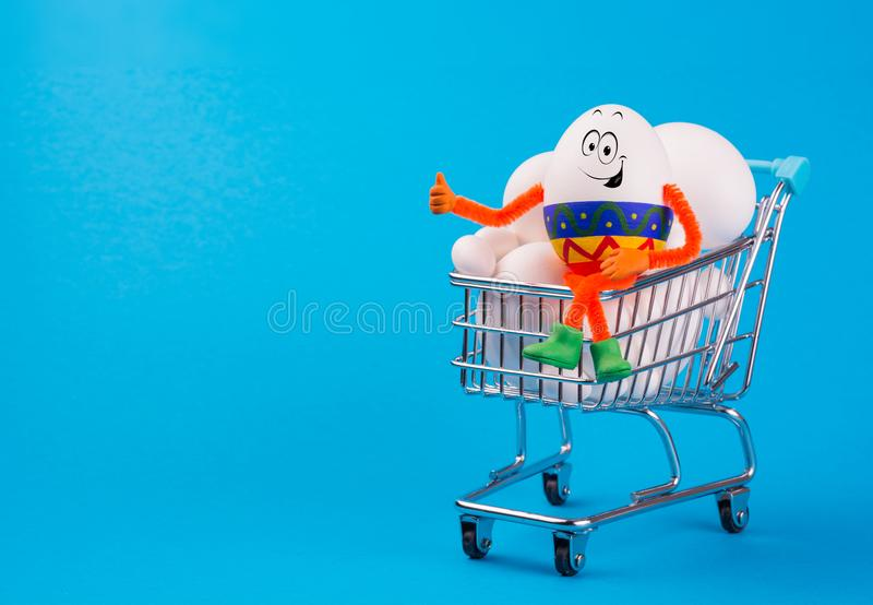 Funny happy smiling egg sitting on a cart full of eggs. And make shopping in a supermarket. Preparation for Easter royalty free stock photos