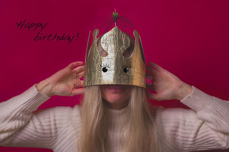 Funny happy woman in gold cardboard crown on the pink background stock photography