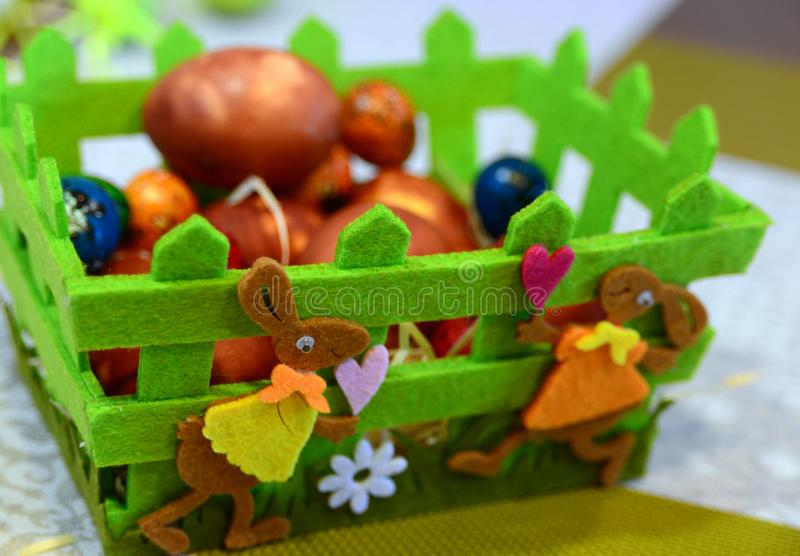Funny hares on a green basket in which to lay Easter eggs. Holy Easter. stock photo