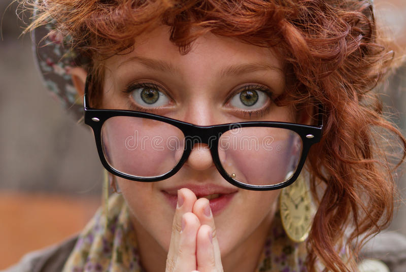Funny hipster girl in eyeglasess. Funny young person in eyeglasses looking at you royalty free stock photo