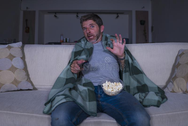 Scared and funny man alone at night in living room couch watching horror scary movie in television screaming and eating popcorn royalty free stock photos