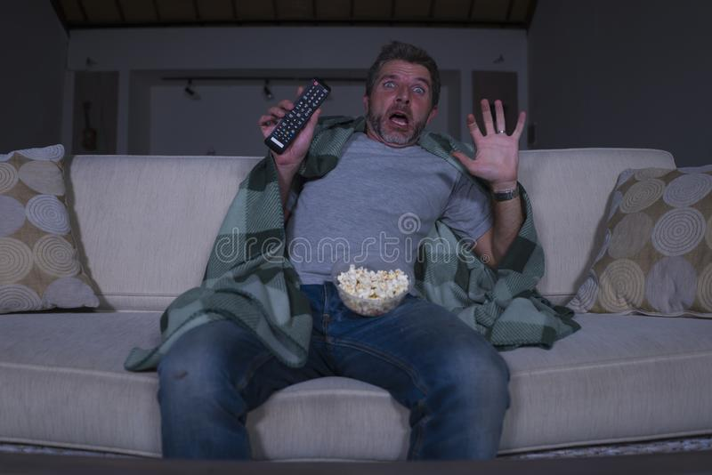 Scared and funny man alone at night in living room couch watching horror scary movie in television screaming and eating popcorn. Funny home lifestyle portrait of stock images