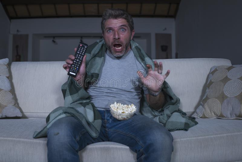 Scared and funny man alone at night in living room couch watching horror scary movie in television screaming and eating popcorn. Funny home lifestyle portrait of stock image