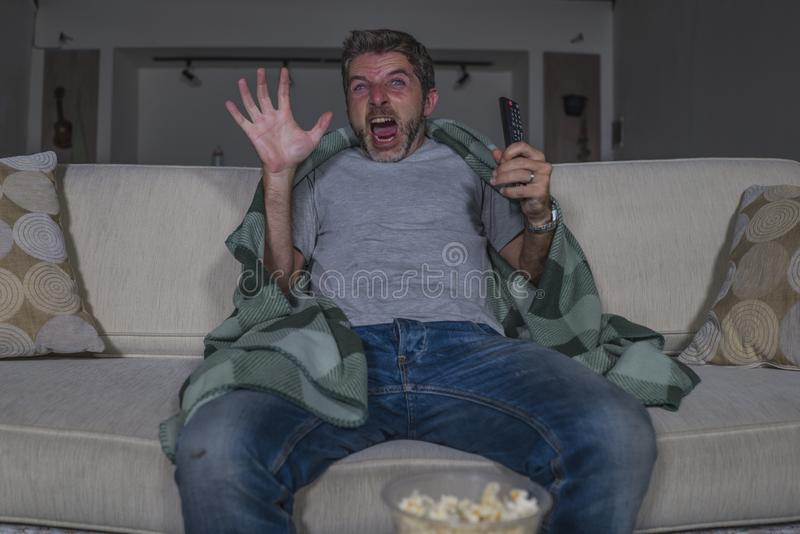 Scared and funny man alone at night in living room couch watching horror scary movie in television screaming and eating popcorn. Funny home lifestyle portrait of royalty free stock photography