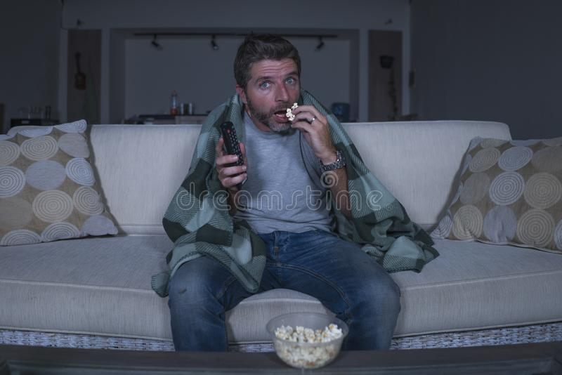Scared and funny man alone at night in living room couch watching horror scary movie or scary show in television eating popcorn. Funny home lifestyle portrait of royalty free stock image