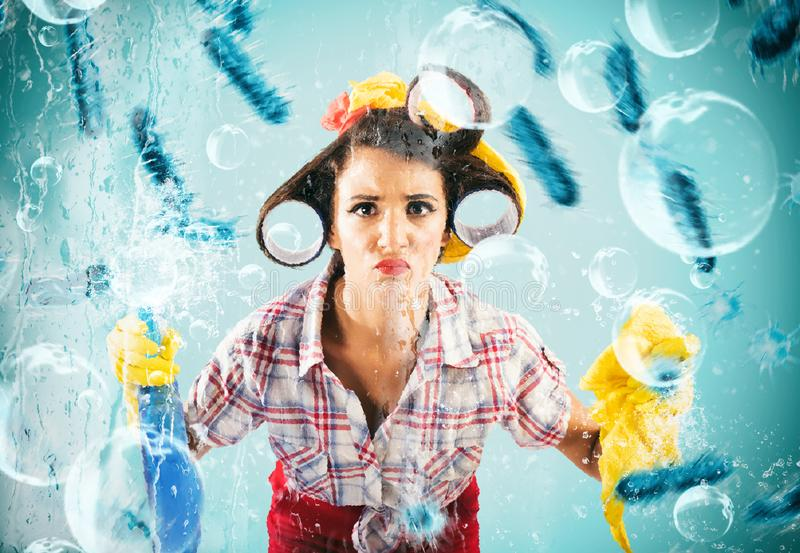 Funny housewife cleans and disinfects to keep germs away. Funny housewife busy in household cleaning with spray disinfectant royalty free stock images
