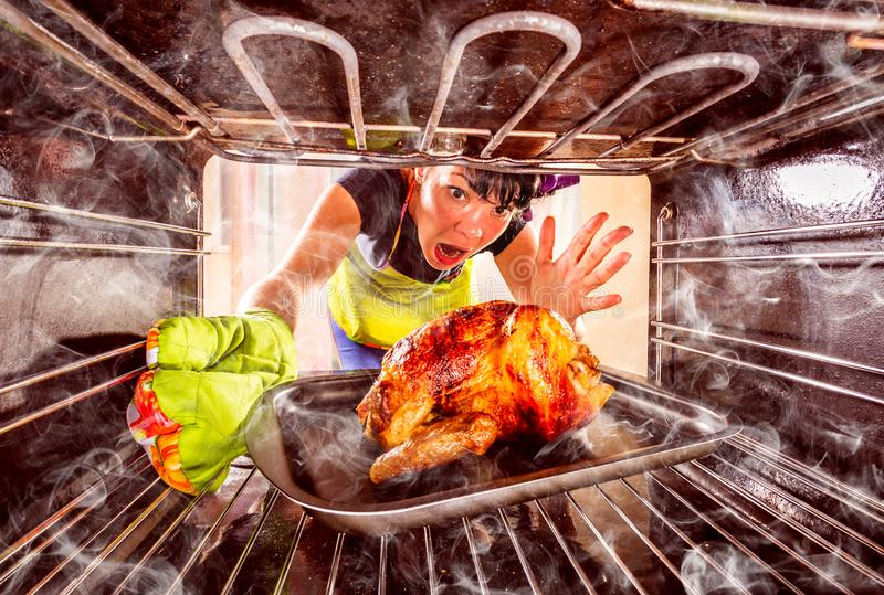 Funny Housewife perplexed and angry. Loser is destiny!. Funny Housewife overlooked roast chicken in the oven, so she had scorched focus on chicken, view from the royalty free stock images