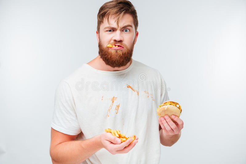 Funny hungry bearded man eating junk food. On white background royalty free stock image