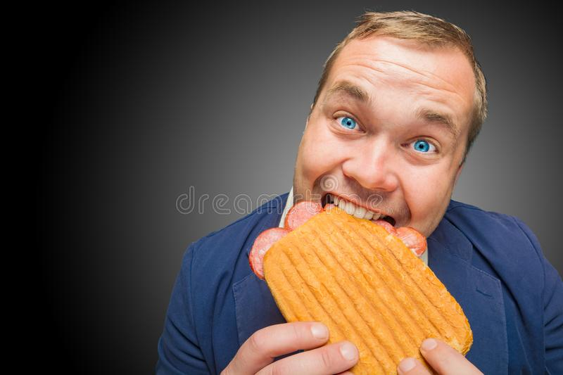 Funny hungry man eating the tasty sandwich royalty free stock images