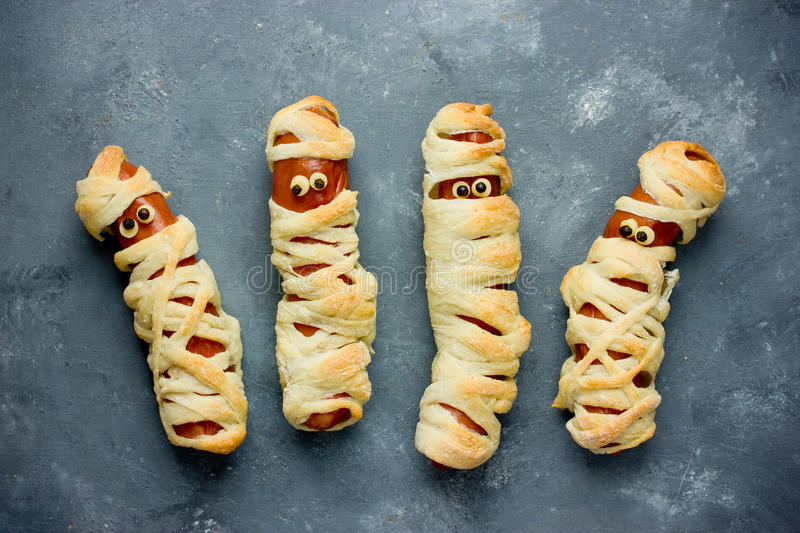 Funny idea for kids for Halloween food - sausage in dough as a m royalty free stock photos