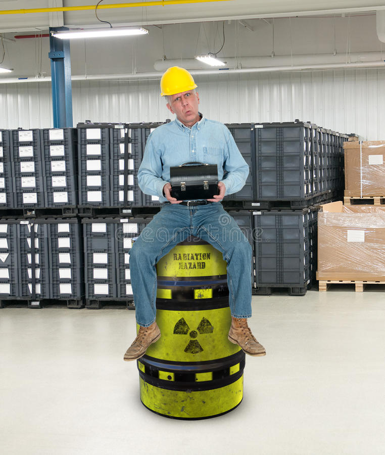 Funny Industrial Worker, Job training. A funny industrial manufacturing factory worker is sitting on a barrel of radioactive material and toxic waste. Job stock image