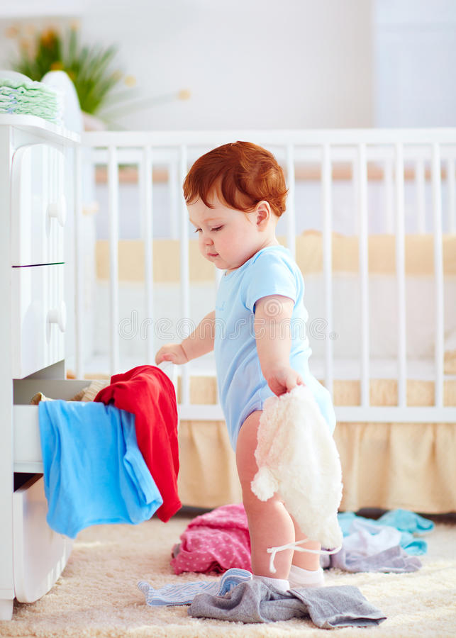 Funny infant baby throwing out clothes from the dresser at home royalty free stock photography