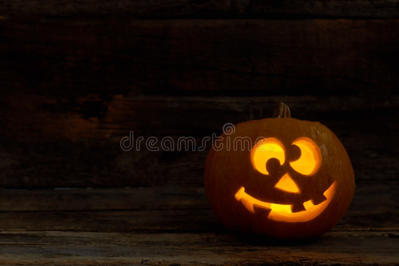 Funny Jack-O-Lantern with glowing candle. Halloween pumpkin face with burning candle on dark background. Halloween holiday celebration royalty free stock photography
