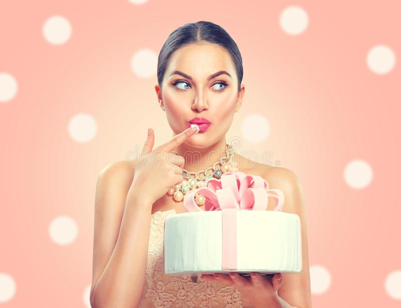 Funny joyful beauty model girl holding big beautiful party or birthday cake over pink background. And tasting it stock image