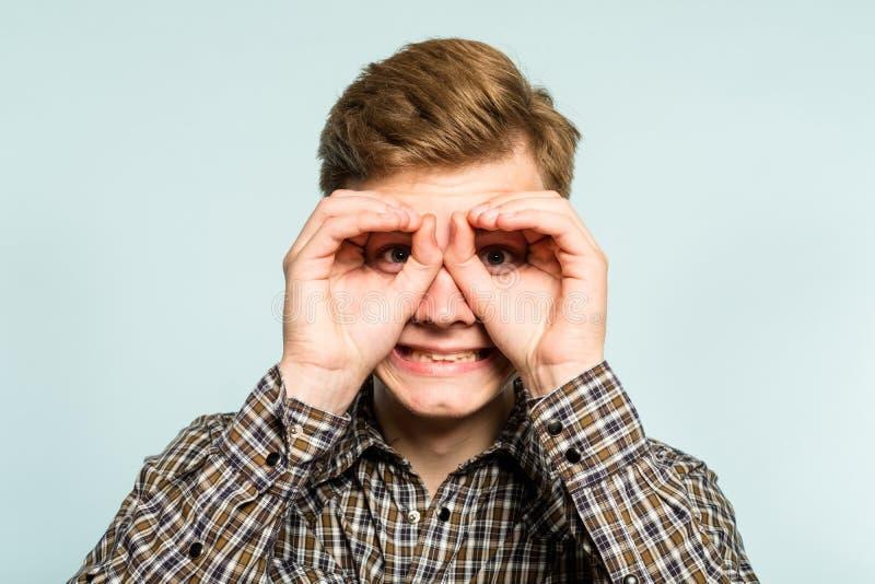 Funny joyful playful man pretend look binocular stock image
