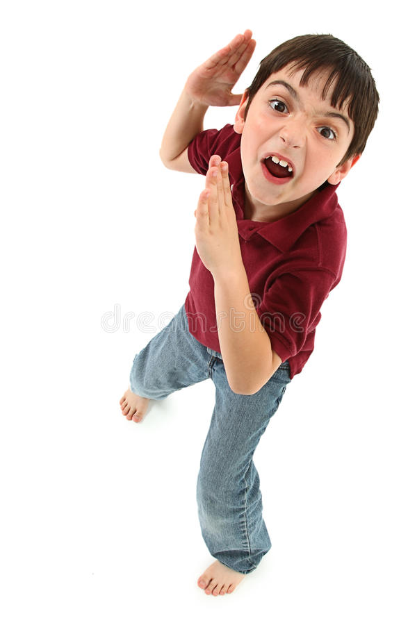 Funny Karate Kid. Adorable 8 year old french american boy making silly karate faces and poses over white background stock photos