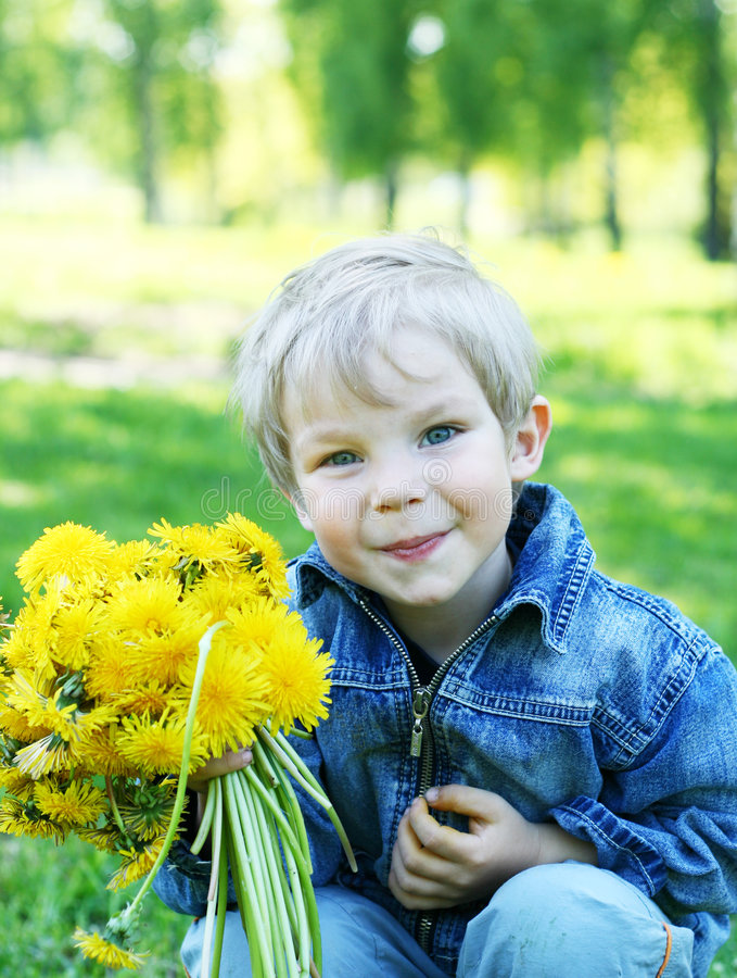 Funny kid. Portrait of funny kid with dandelions stock image