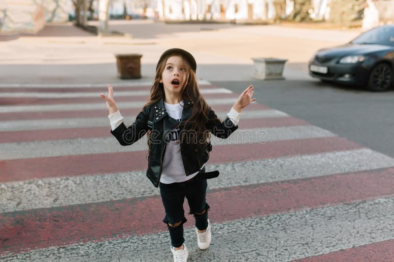 Funny kid with beautiful long hair running to the camera on the crosswalk and looking away. Cute little girl in trendy royalty free stock images