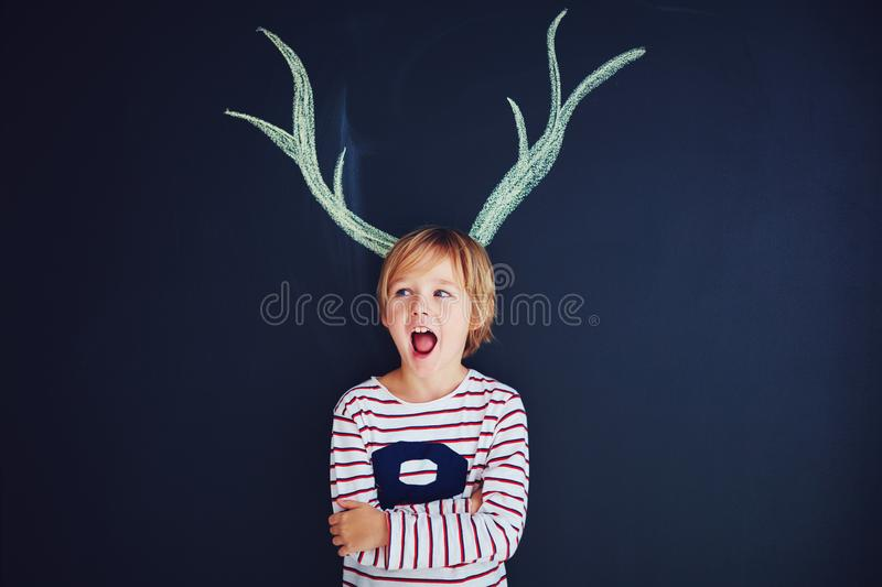 Funny kid, boy with drawn antlers standing in front of a chalk wall. Funny excited kid, boy with drawn antlers standing in front of a chalk wall stock photography