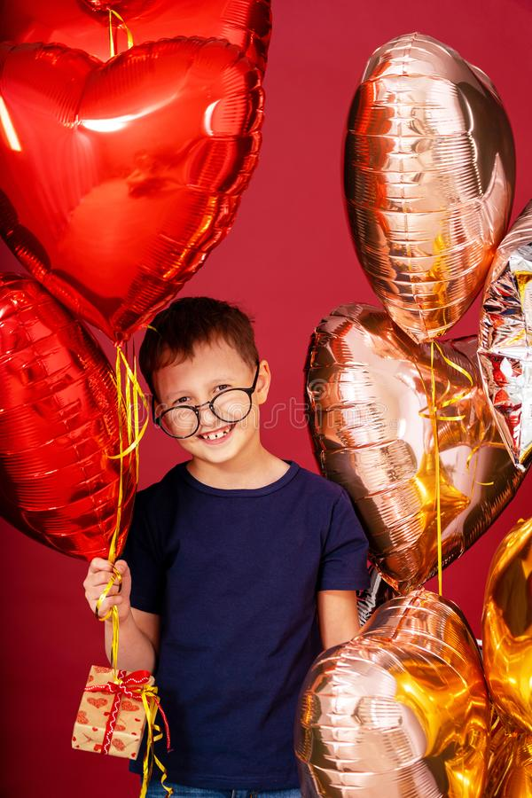 Funny kid boy in glasses, different color heart, star balloons for valentines day or birthday on red background with free text stock images