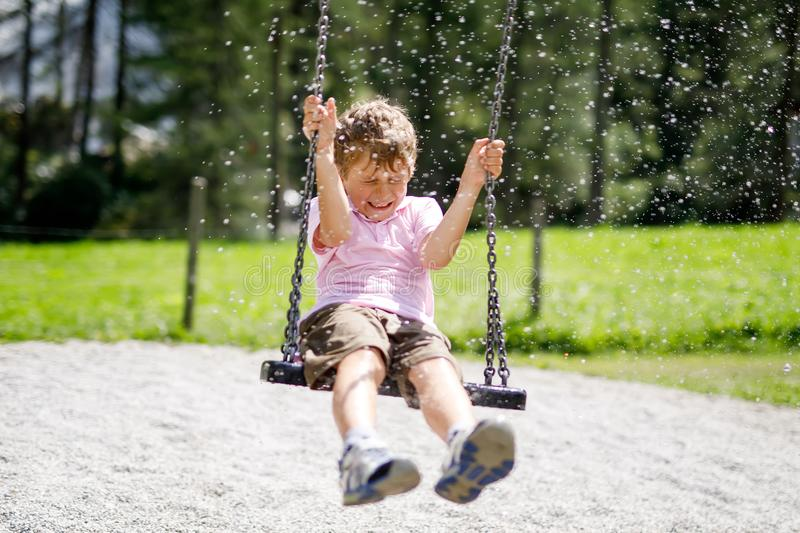 Funny kid boy having fun with chain swing on outdoor playground while being wet splashed with water. Child swinging on summer day. Active leisure with kids royalty free stock photography
