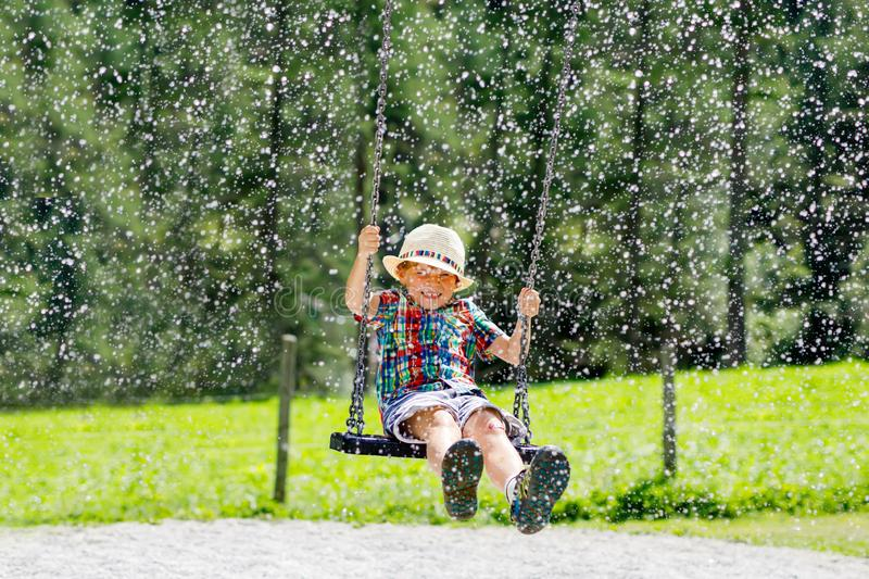 Funny kid boy having fun with chain swing on outdoor playground while being wet splashed with water. child swinging on. Summer day. Active leisure with kids stock images