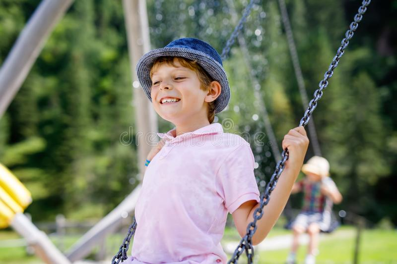 Funny kid boy having fun with chain swing on outdoor playground while being wet splashed with water. child swinging on. Summer day. Active leisure with kids stock photo