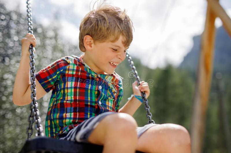 Funny kid boy having fun with chain swing on outdoor playground while being wet splashed with water. child swinging on. Summer day. Active leisure with kids royalty free stock image