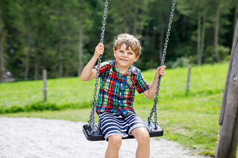 Funny kid boy having fun with chain swing on outdoor playground while being wet splashed with water. child swinging on. Summer day. Active leisure with kids stock photography