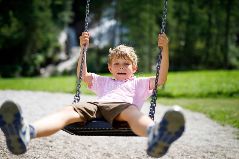 Funny kid boy having fun with chain swing on outdoor playground while being wet splashed with water. child swinging on. Summer day. Active leisure with kids royalty free stock photos