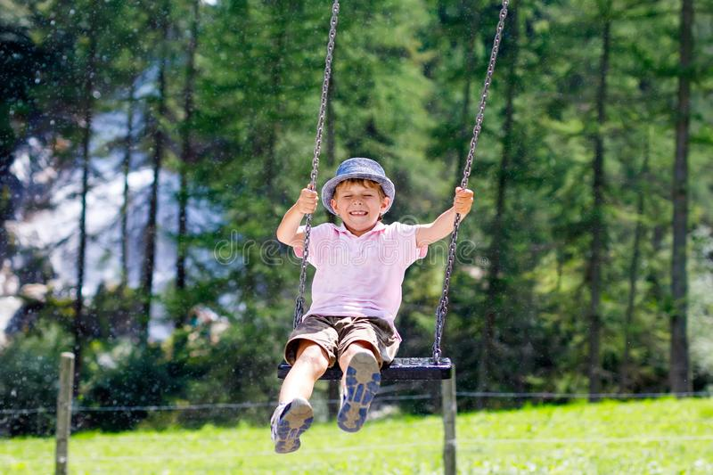 Funny kid boy having fun with chain swing on outdoor playground while being wet splashed with water. child swinging on. Summer day. Active leisure with kids royalty free stock images