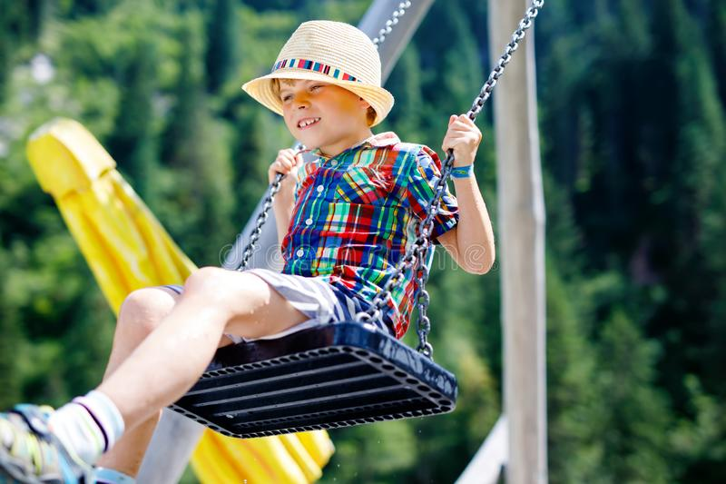 Funny kid boy having fun with chain swing on outdoor playground while being wet splashed with water. Child swinging on summer day. Active leisure with kids stock image