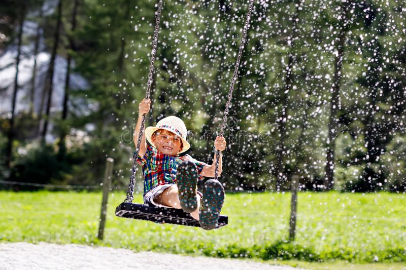 Funny kid boy having fun with chain swing on outdoor playground while being wet splashed with water. Child swinging on summer day. Active leisure with kids royalty free stock images