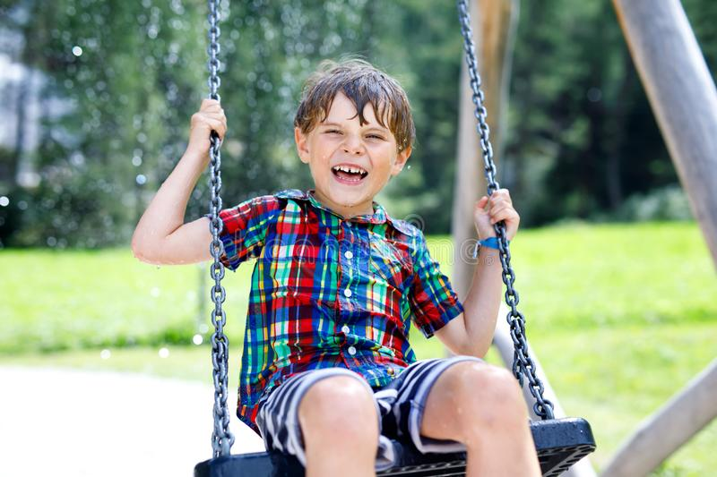 Funny kid boy having fun with chain swing on outdoor playground while being wet splashed with water. Child swinging on summer day. Active leisure with kids stock images