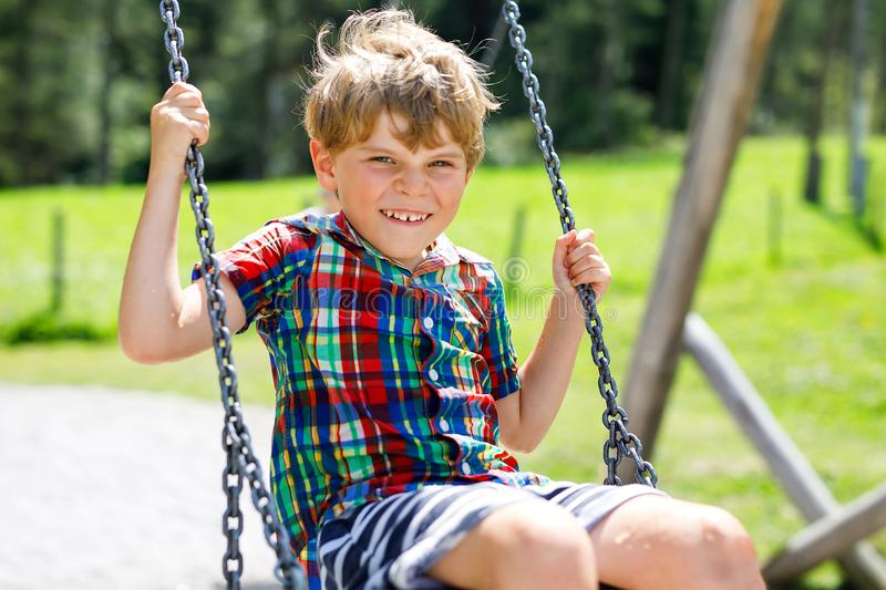Funny kid boy having fun with chain swing on outdoor playground while being wet splashed with water. Child swinging on summer day. Active leisure with kids royalty free stock image