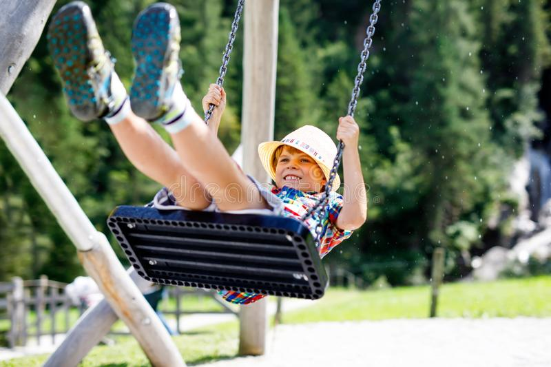Funny kid boy having fun with chain swing on outdoor playground while being wet splashed with water stock images