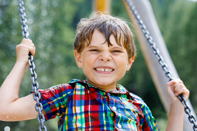 Funny kid boy having fun with chain swing on outdoor playground while being wet splashed with water. Child swinging on summer day. Active leisure with kids stock photos