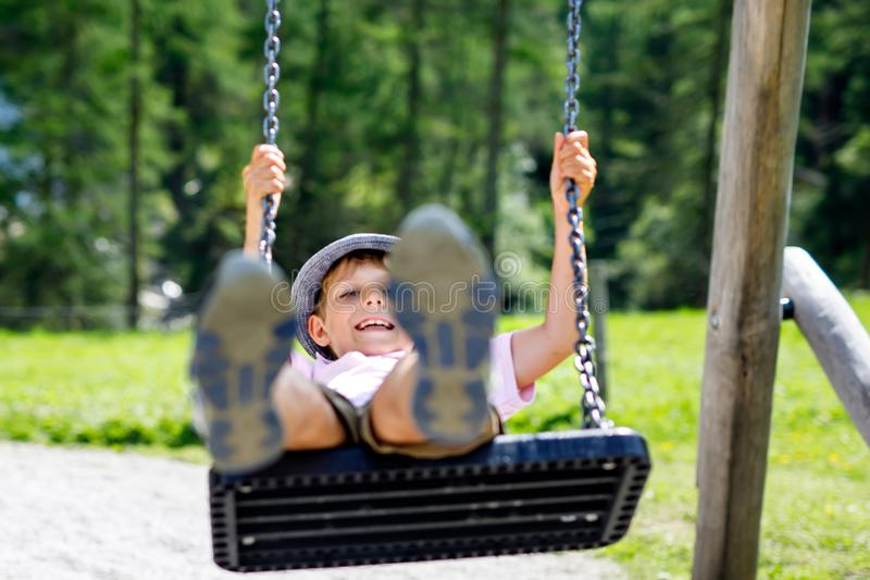 Funny kid boy having fun with chain swing on outdoor playground while being wet splashed with water. Child swinging on summer day. Active leisure with kids royalty free stock photos